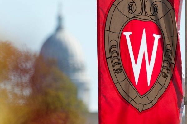 A 'W' crest banner hanging on Bascom Hill at the University of Wisconsin is pictured in relation to an out-of-focus view of the Wisconsin State Capitol dome during autumn.