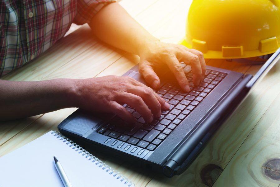 Man using laptop with yellow helmet on table