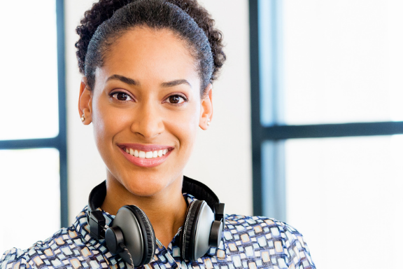 Close up image of woman smiling looking at camera with headphone around her neck.
